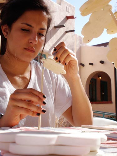 Maria Fallon paints a clay flower at Bens Bells, a nonprofit organization in Tucson. The organization relies heavily on volunteers to help create the ceramic bells they hang around the city.