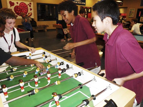 Anthony Taylor, Damon Jaines, Chase Herzog and Gabe Oro Peza play foosball at the Frank and Edith Morton Clubhouse.