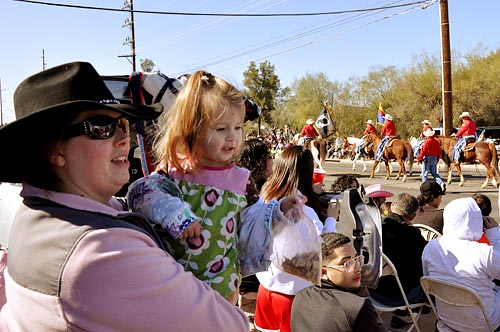 Luann Read and her daughter Lavita, 1, try to catch a glimpse of the parade at the 85th La Fiesta de los Vaqueros Rodeo Parade. Reed joined thousands of Tucsonans the shortened parade route.