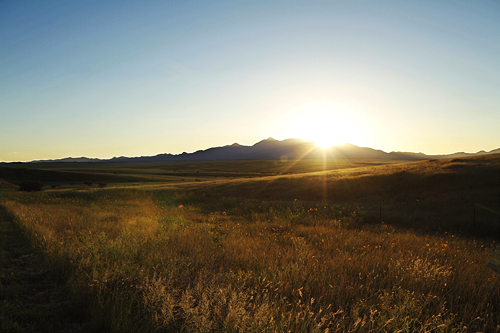 The sun sets behind grassy, rolling hills and purple mountains a few miles west of Sonoita, AZ.
