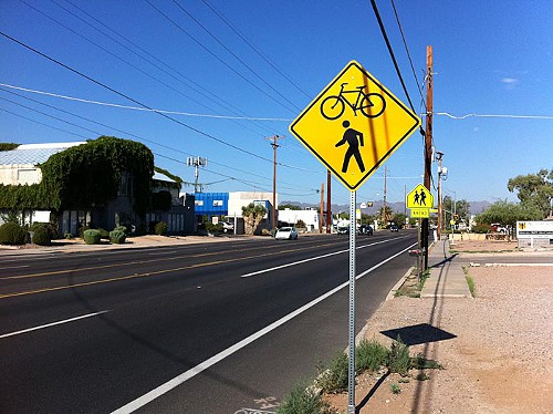 Signs along the roadway alert motorists to expect both bicycles and pedestrians in the crossing.